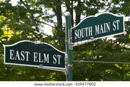 Pretty streets signs for the corner of Main and Elm in a small town.