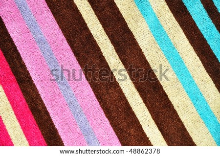 pretty striped beach towel useful as a background texture - stock photo