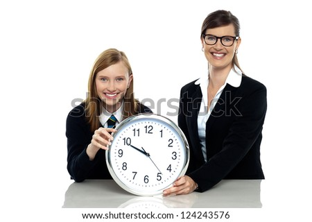 Pretty student holding clock with her teacher isolated against white background. - stock photo