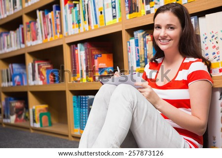 Pretty student sitting on floor in library at the university - stock photo