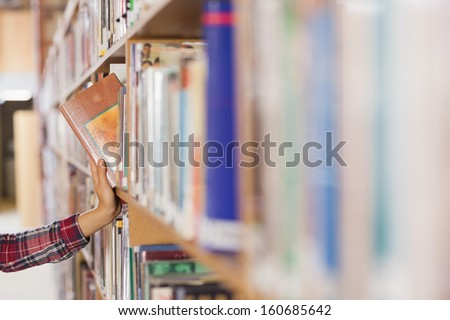 Pretty student taking book out of shelf in library - stock photo
