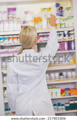 Pretty student taking box from shelf in the pharmacy - stock photo