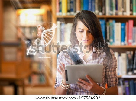 Pretty student using futuristic interface to learn about science from digital tablet standing in college library - stock photo