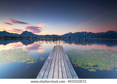 pretty summer sunset at lake Starnberger in bavarian alps. The long jetty leads out in to the lake