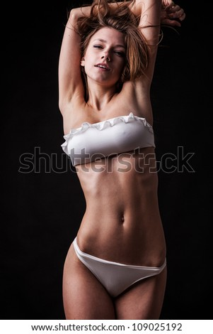 Pretty tanned woman in bikini on black background. - stock photo