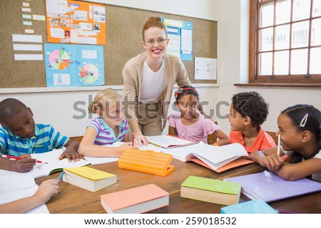 Pretty teacher helping pupils in classroom at the elementary school