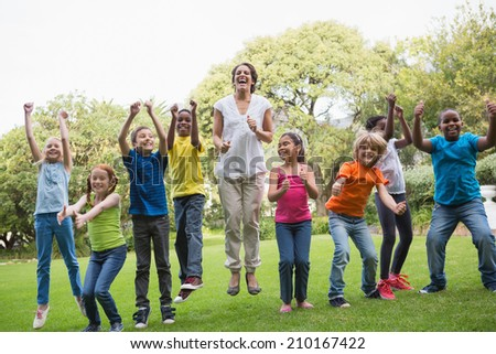 Pretty teacher jumping with pupils outside at the elementary school - stock photo