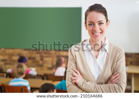 Pretty teacher smiling at camera at back of classroom at the elementary school - stock photo
