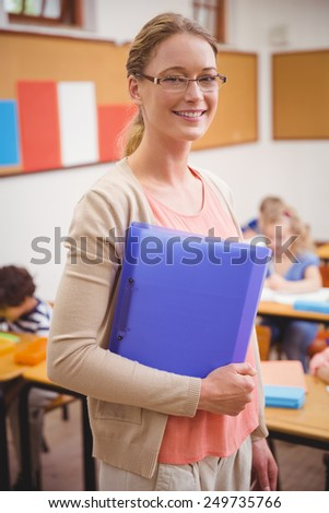 Pretty teacher smiling at camera while holding folder at the elementary school - stock photo