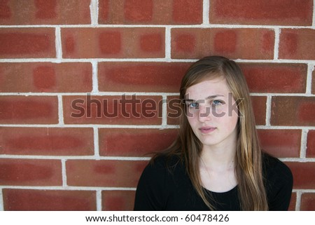 pretty teen girl against brick wall