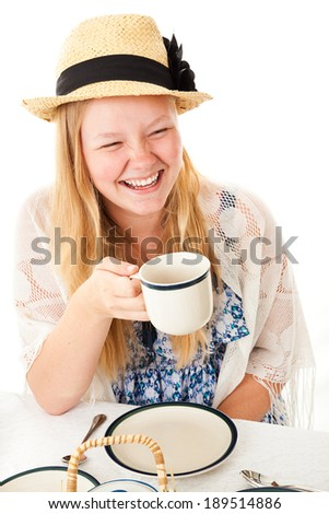 Pretty teen girl dressed for a tea party, laughing at her companion off camera.  Isolated on white. - stock photo
