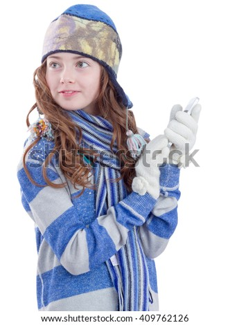 Pretty teen girl in winter clothes with smartphone
