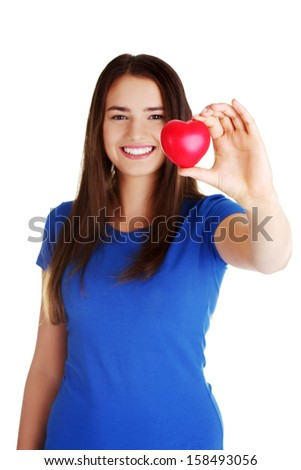 Pretty teen girl showing red heart in her hand over white.  - stock photo
