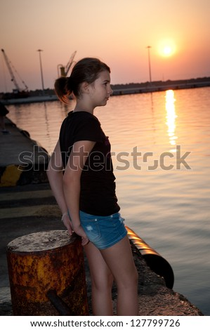 pretty teen girl sitting on a dock looking into the sea at sunset .Lonely teenage girl sitting on  dock and looking at the ocean - stock photo