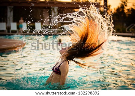 Pretty teen girl whipping her hair back in the pool and spraying water everywhere - stock photo