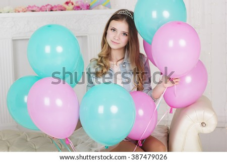 Pretty teen girl with many blue and pink balloons - stock photo