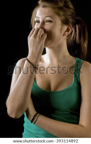 Pretty teenage girl laughing, covering face
