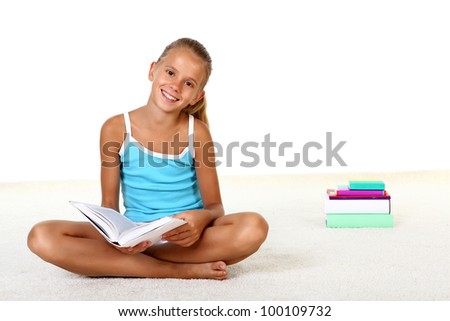 Pretty teenage girl sitting on th efloor with study books - stock photo