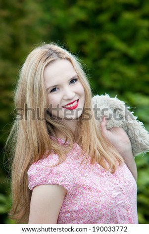 Pretty teenage girl with a charming smile wearing a pink summer top posing against a leafy green bush with a jacket slung over her shoulder - stock photo