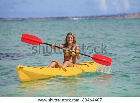 pretty teenage girl with her kayak paddling in the warm Pacific waters of Hawaii - stock photo