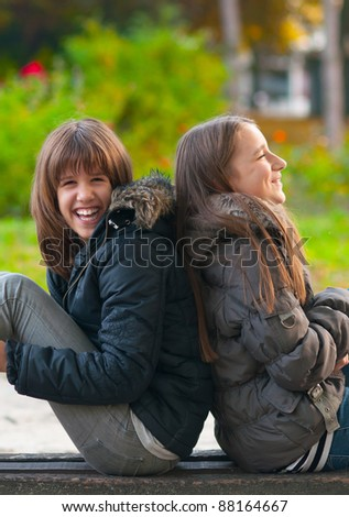 Pretty teenage girls laughing and joking while sitting in the park on beautiful autumn day.