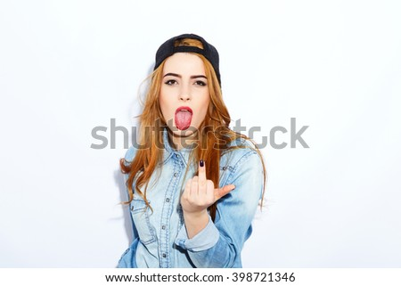 Pretty teenage red-haired girl with long hair wearing blue shirt and cap showing middle finger and tongue, emotions, copy space, white background, pathos style.