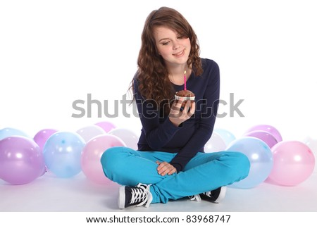 Pretty teenager girl celebrates happy birthday with a chocolate cup cake and single pink candle, sitting among party balloons with a happy smile.