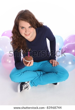 Pretty teenager girl celebrates happy occasion with a chocolate cup cake and single pink candle, sitting among party balloons looking up to the camera.