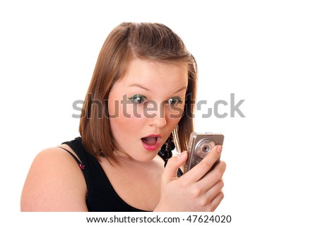 Pretty teenager girl shocked by message - stock photo