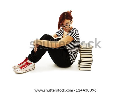 Pretty teenager girl sit on floor and reading book. Isolated on white background - stock photo