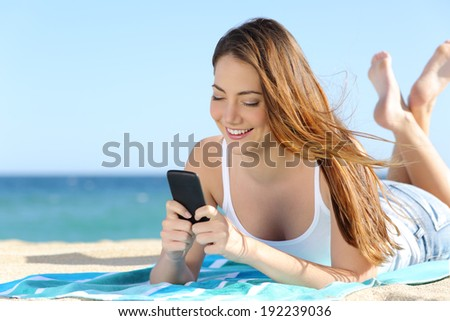 Pretty teenager girl using a smart  phone lying on the beach with the sea and horizon in the background             - stock photo