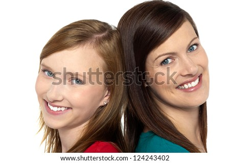 Pretty teenager girl with her mother. Posing back to back. - stock photo