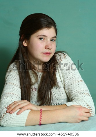 pretty teenager girl with long thick brown hair close up portrait on blue wall background - stock photo