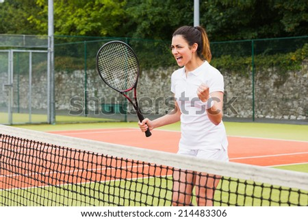 Pretty tennis player celebrating a win on a sunny day - stock photo