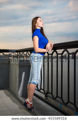 Pretty thoughtful brunette posing near the river - stock photo