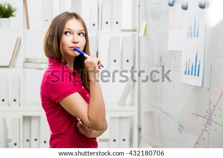 Pretty thoughtful woman in bright casual shirt standing in office next to whiteboard with business charts and graphs - stock photo