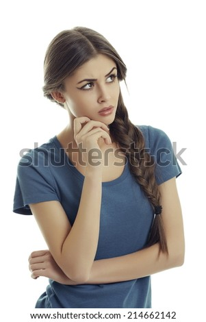 Pretty thoughtful young woman with long brown braided hair looking up over white background. - stock photo