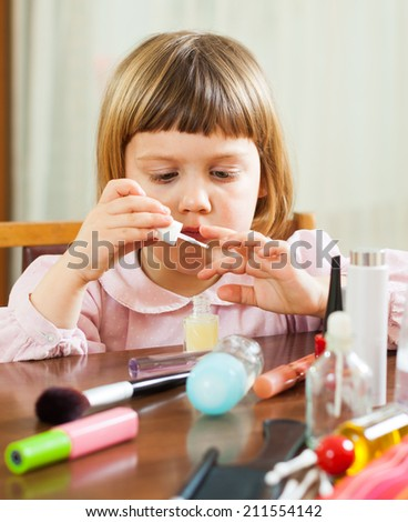 Pretty three year old girl making manicure - stock photo