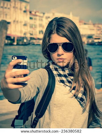Pretty tourist girl in sunglasses taking self portrait with the Grand Canal in the background. Venice. Italy - stock photo