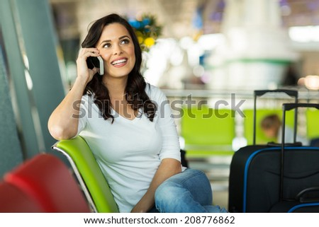 pretty traveller making a phone call at airport - stock photo
