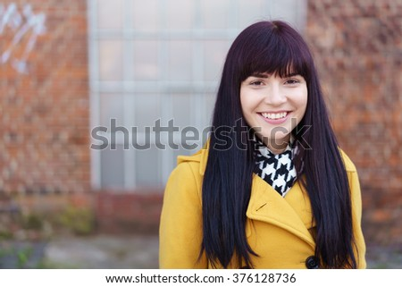 Pretty trendy young woman with long brunette hair and a gorgeous smile wearing a bright yellow jacket posing in front of an exterior brick wall - stock photo