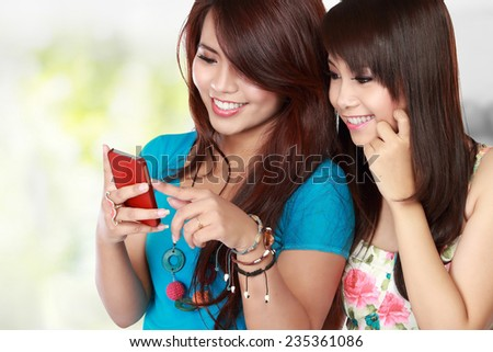 Pretty two Asian Woman text on her cellphone with happy face - stock photo