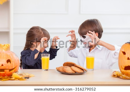 Pretty two siblings are grinning their teeth with threats. They are celebrating Nut-Crack night. The boy and girl are sitting at the table near food and pumpkin. They are drinking juice - stock photo