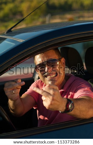 Pretty upset driver  doing obscene gestures - stock photo