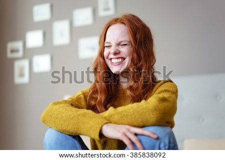 Pretty vivacious young woman laughing with her eyes screwed closed in a candid moment of fun and hilarity as she sits on her bed at home - stock photo