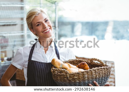 Pretty waitress carrying basket of bread at the bakery - stock photo