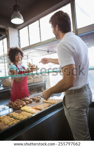 Pretty waitress giving food to customer at the bakery - stock photo