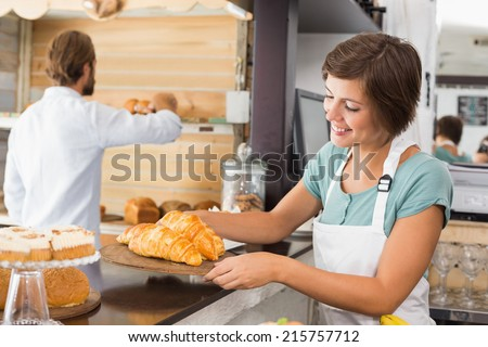 Pretty waitress holding tray of croissants at the coffee shop - stock photo