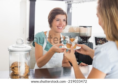 Pretty waitress serving muffin to customer at the coffee shop - stock photo