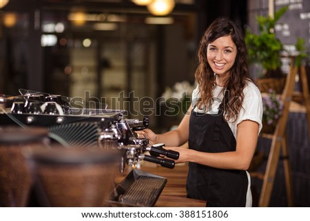 Pretty waitress using the coffee machine at the coffee shop - stock photo